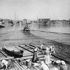 I. K. Inhan valokuvassa vaatteiden pesua Nalkalan rannassa Pyhäjärvellä Ratinan suvannon kohdalla Tampereella