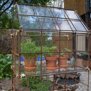 Ett litet örtväxthus byggt av armeringsjärn och pleciglas med tre terrakottakrutor med örter i.