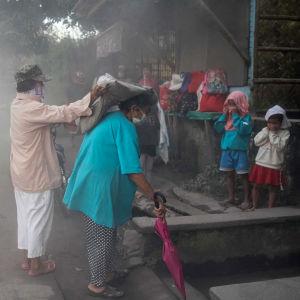 Människor i staden Guinobatan täcker sina ansikten för att skydda sig mot askan.