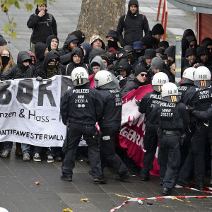 Kravallpolis knuffas med demonstranter i Köln 22.4.2017