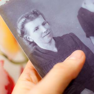 Vanhaa valokuvaa pidellään käsissä.