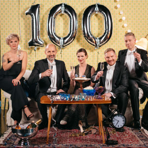 Tre män i frack och två kvinnor i festklädsel sitter i soffa och skålar mot kameran
