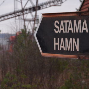 En skylt där det på svart botten står med vita bokstäver SATAMA HAMN, i bakgrunden skymtar kranar och hav.