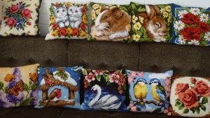 korsstygnsarben, tio prydnadskuddar i korsstygnsbroderi i en soffa