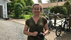 Nina Gustafsson med kameran i handen framför trädgården.