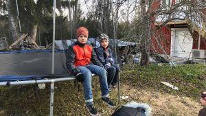 William och Alfred Grönlund sitter på studsmattan på gården.