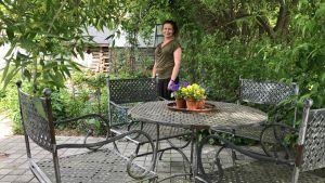 Nina Gustafsson i trädgårdet bakom ett möblemang.