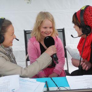 Yle Jyväskylän Radio-kylässä -kierroksella toimittajat Marika Paaso ja ja Heli Kaski haastattelevat 7-vuotiasta Iina Kangasta Konnevedellä kesällä 2013