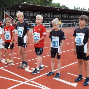 Flera unga löpare står färdiga på startstrecket.