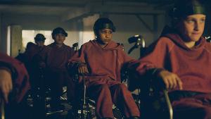 Melanie (Sennia Nanua) sitter fastspänd i en rullstol tillsammans med en massa andra barn i ett mörkt klassrum.