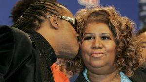 Stevie Wonder ger Aretha Franklin en puss på kinden.