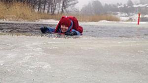 Yle nyheters reporter Sara Ekstrand provar hur det är att gå igenom isen.
