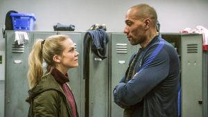 Helena och Michael tittar på varandra med bestämda miner i omklädningsrummet.
