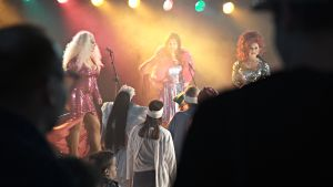 Tummien hahmojen takaa näkyy yleisöä ja kolme drag-artistia lavalla.