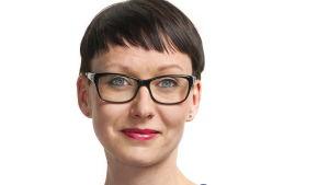 Lyhythiuksinen, tumma, silmälasipäinen nainen kasvokuvassa.
