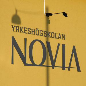 Yrkeshögskolan Novias skylt på gul vägg.