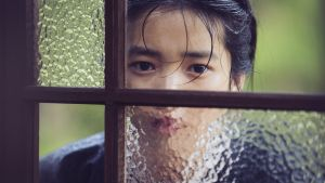Tjänsteflickan Sok-Hee (Tae-ri Kim) kikar in genom ett fönster.