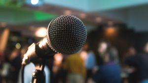 En mikrofon med en suddig bakgrund av en folkmassa.