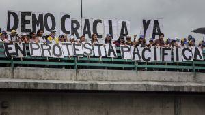Människor står på en bro och protesterar mot landets ledning i Caracas, Venezuela den 1 juli 2017.