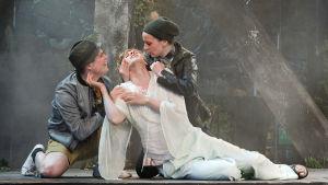 Helena omgiven av Demetrius och Lysander i Ryhmäteatteris uppsättning av En midsommarnattsdröm.