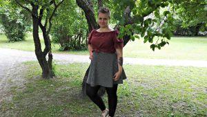 sara westerlund, admin för en stor facebookloppisgrupp, står i grönskan under ett träd