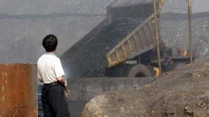 En kille tittar på när kol utvinns i Kina, bilden är tagen juli 2005.