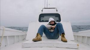 Samuele sitter på båtdäcket och mår illa.