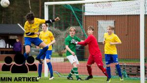 Fem killar framför ett fotbollsmål. Killen längst till vänster knoppar bollen.