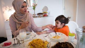 En muslimsk kvinna med sin dotter äter kvällsmålet iftar under ramadan.