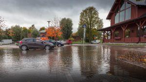 Bilar på en översvämmad parkeringsplats. Höstlandskap, en stor röd träbyggnad till höger.