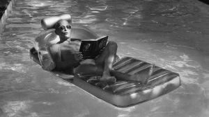 Svartvit bild av Schein i en pol där han på en badmadrass läser en bok.