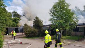 Flera brandmän släcker en radhusbrand.