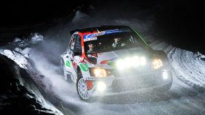 Rallybil kommer susande på snötäckt väg på natten.