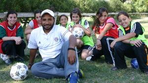 Aleksandrialaisen Sporting-joukkueen tyttöjä futisharjoitusten tauolla valmentajan kanssa.