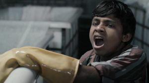 12-årig indisk industriarbetare har svårt att hålla sig vaken i textilfabrik.