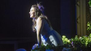 Julia (Satu Tuuli Karhu) kukkien peittämällä parvekkeellaan.