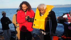 Miguiz Nicolas från Proactiva Open Arms hjälper en äldre man med skidat ben upp på stranden.