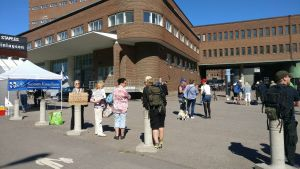 Några av Ilja Janitskins anhängare är samlade i solen utanför Helsingfors tingsrätt.