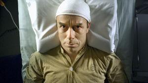 Risto Kaskilahti makaa sängyssä pää kääreessä.