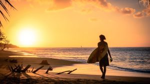 Surfare på karibisk badstrand.