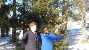 Grundarna till Lively Air Jouno Auri och Rathan Kumar står i en skog och håller i varsin flaska med luft från Finland.