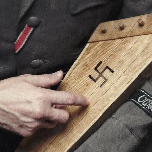 SS-univormuun pukeutunut mies näppäilee hakaristillä koristettua kannelta