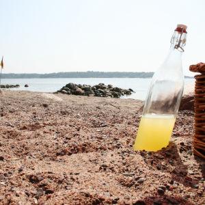 badstrand och en flaska lemonad invid en picknickkorg