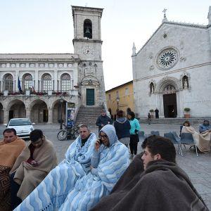 Några män insvepta i filtar sitter på ett torg.