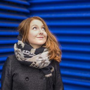 Tiia Ung katsoo yläviistoon sinisen metalliseinän edessä.