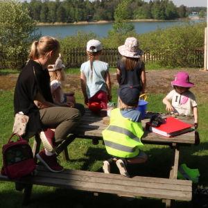 Amelie Lund, föreståndare på daghemmet Tallbo sitter utomhus runt ett bord med daghemsbarn.