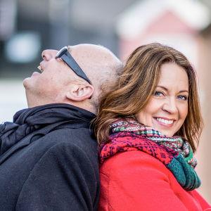 Programledarna Gert och Pernilla står med ryggarna mot varandra och skrattar.