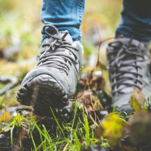 Person vandrar i naturen, närbild på skorna.
