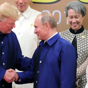 Donald Trump och Vladimir Putin skakar hand.