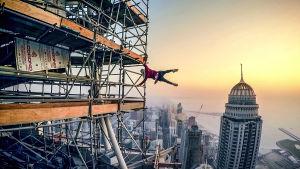 Malesialainen Abudi roikkuu rakennustelineellä pilvenpiirtäjien huippujen yllä.